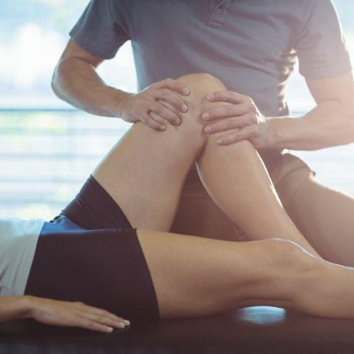 En esta foto aparece un fisio tratando la rodilla de un paciente